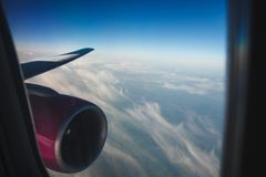 Wing of aircraft with a pink engine against the sky. feathery clouds from window porthole. mood of vacation. Wing of aircraft with a pink engine against the sky Royalty Free Stock Photos