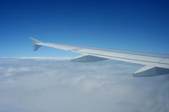 Wing of aircraft in sky. Aerial view of aircraft wing flying over clouds in sky royalty free stock photography