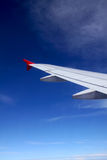 Wing of an airplane. With red winglet against blue sky royalty free stock photo