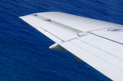 Wing of an airplane above the Ocean Royalty Free Stock Photo