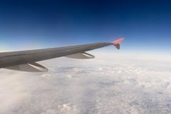 Wing of an airplane above solid clouds Stock Photos