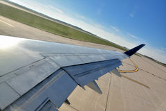 Wing of airplane and airport runway. Airplane wing before flight, and airport runway, shown as travel concept, departure, start of trip, or industrial of Royalty Free Stock Photos