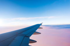 Wing of the airplane on blue and pink sky background. The wing of the airplane on a blue and pink sky background Stock Image