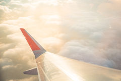 Wing of airplane on cloud sky from window in morning. Stock Photos