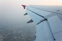 Wing of an airplane flying Stock Photos