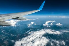 Wing of an airplane flying above clouds Royalty Free Stock Photo