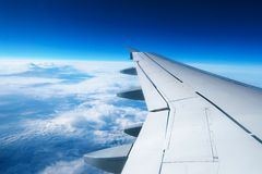 Wing of an airplane flying above the clouds Royalty Free Stock Photos
