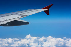 Wing of an airplane. Flying above the clouds royalty free stock photo