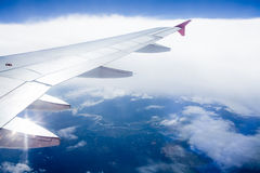Wing of an airplane flying above the clouds Stock Photos
