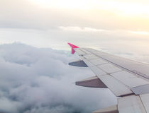 Wing of an airplane flying above Stock Photo