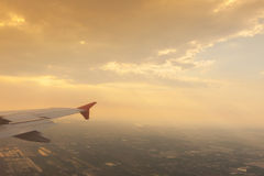 Wing of airplane flying above the clouds . Royalty Free Stock Photo