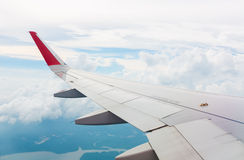 Wing of an airplane flying above the clouds atmosphere Royalty Free Stock Image