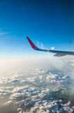 Wing of an airplane flying above the clouds Stock Photography