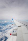 Wing of an airplane flying above clouds Stock Photography