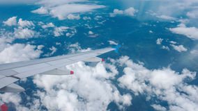 Wing of an airplane flying above clouds Stock Images