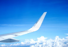 Wing of airplane flying above the clouds and blue sky Royalty Free Stock Images