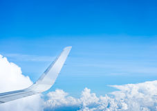 Wing of airplane flying above the clouds and blue sky Royalty Free Stock Photos