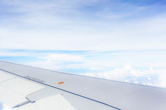 Wing of airplane flying above clouds blue sky background Stock Photo