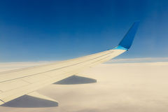 Wing of an airplane flying above the clouds Royalty Free Stock Photography
