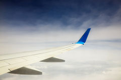Wing of an airplane flying above the clouds Royalty Free Stock Image
