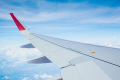 Wing of airplane flying above clouds blue sky background Royalty Free Stock Photos