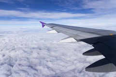 Wing of an airplane flying above the clouds Stock Images