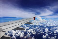 Wing of an airplane flying above the clouds Royalty Free Stock Images