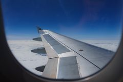 Wing of an airplane flying above the clouds look Stock Photography