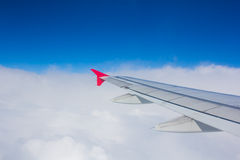 Wing airplane flying above clouds looking at the sky from the wi Royalty Free Stock Photos