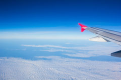 Wing airplane flying above clouds looking at the sky from the wi Stock Photo
