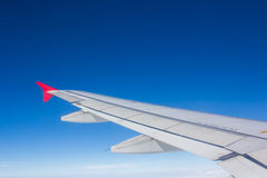 Wing airplane flying above clouds looking at the sky from the wi Royalty Free Stock Photo