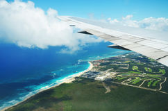 Wing of an airplane flying above the clouds over tropical island Stock Photo
