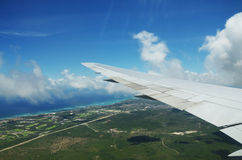 Wing of an airplane flying above the clouds over tropical island Royalty Free Stock Photos