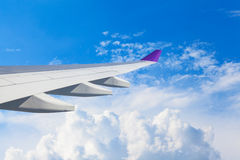 Wing of an airplane flying above the clouds. people looks at the Royalty Free Stock Images