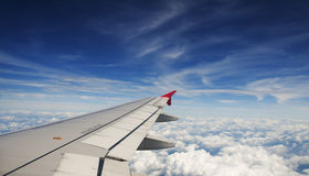 Wing of an airplane. Flying above the clouds. people looks at the sky from the window of the plane, using airtransport to travel Royalty Free Stock Photography