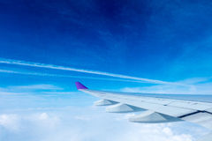 Wing of an airplane flying above the clouds Stock Photo