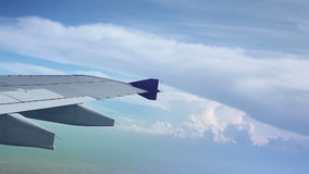 Wing of an airplane flying above the clouds, shot from the window of the plane. Wing of an airplane flying above the clouds , shot from the window of the plane stock video footage