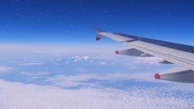 Wing of an airplane flying above the clouds stock video footage