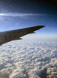 Wing of airplane flying above clouds Royalty Free Stock Photography
