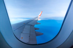 Wing of airplane flying above the clouds Royalty Free Stock Photography