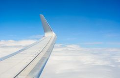 Wing of an airplane flying above the clouds Stock Image