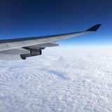 Wing of airplane flying above the clouds in the sky Royalty Free Stock Images