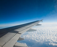Wing of airplane flying above the clouds Royalty Free Stock Images