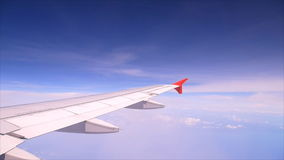 Wing of airplane flying above clouds stock footage