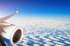 Wing of airplane flying above the clouds in the sky. Royalty Free Stock Photos