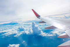 Wing of an airplane flying above the clouds view Royalty Free Stock Photo
