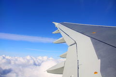 Wing of airplane flying above the clouds Royalty Free Stock Image