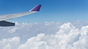 Wing of airplane flying above the clouds Stock Photography