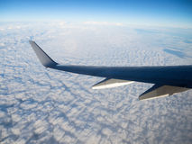 Wing of airplane flying above the clouds Stock Photo