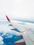 Wing of an airplane flying above the clouds Royalty Free Stock Photo